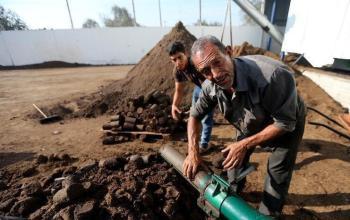 رجل فلسطيني يحمل فحم حجري من تفل الزيتون