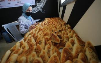 فلسطينيات صُمّ يرتدين ملابس واقية وأقنعة يحضرن المعجنات والبيتزا