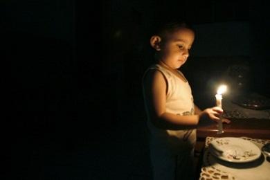 طفل ينير شمعة لانقطاع الكهرباء في غزة