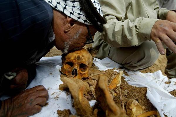 والد أحد الشهداء يقبل عظام ابنه بعد عودتها من مقابر الأرقام