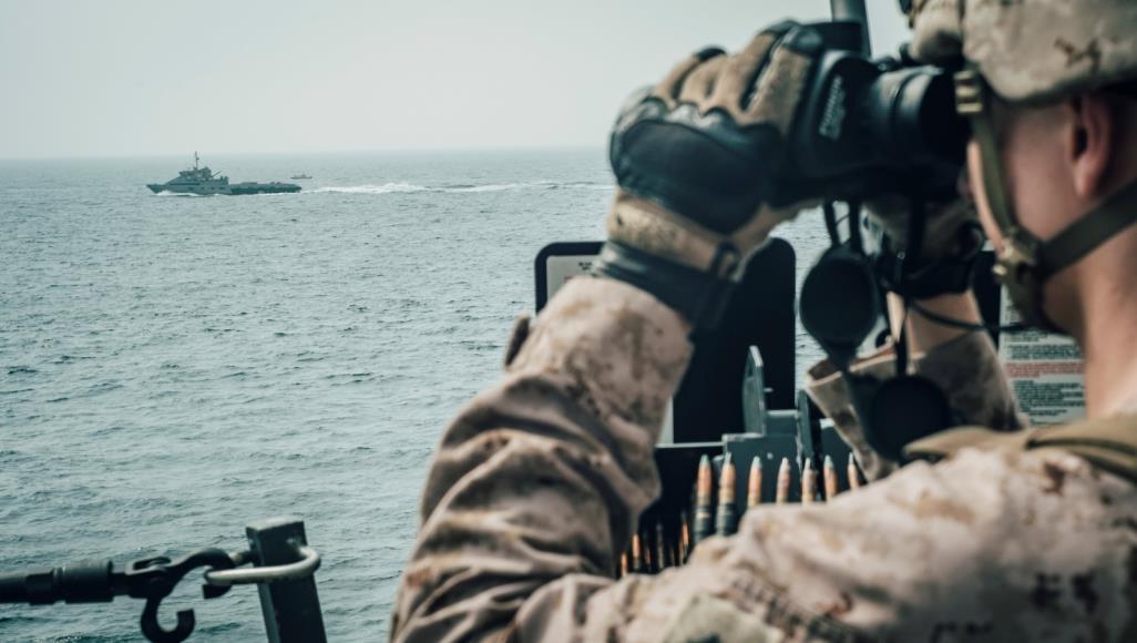 جندي أمريكي يراقب قاربا ايرانيا بمضيق هرمز